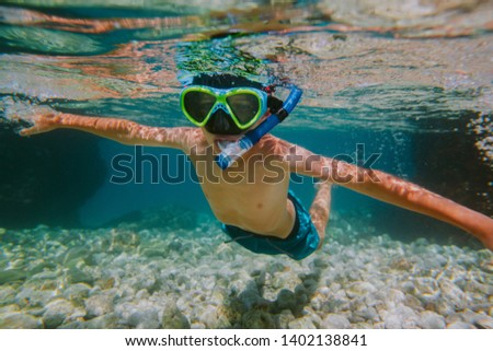 Child snorkeling. Young boy wearing diving mask and snorkel floating in shallow sea with arms spread wide. #1402138841