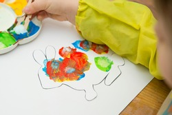 child stamping on white paper  an Easter bunny stencil with painting. Activities at home. What to do with kids at home.
