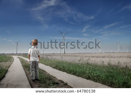 Child standing in front of wind turbines