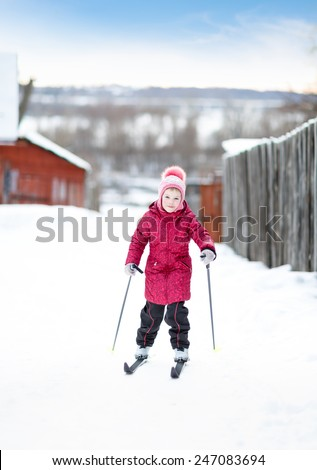 child standing in winter outfit with skis #247083694