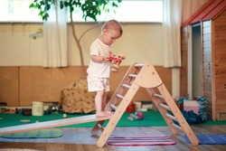 Child standing on a Pikler triangle with a red toy car in a playroom