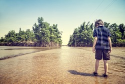 Child standing on flooded road in rural America after a springtime flood with vintage filtered effect