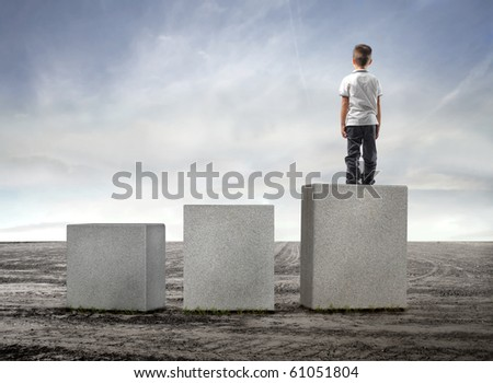 Child standing on the highest of three cubes on a field