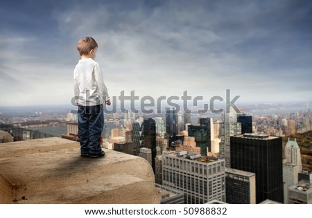 Child standing on the top of a skyscraper and observing the city below