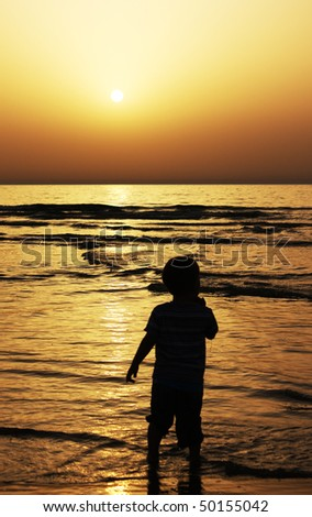 child stands in the sea and watching the sunset