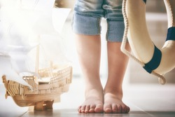 Child stands next to a model ship. Dreams of sea, adventures and travel.