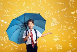 Child student with blue umbrella cover himself from a rain of math and algebra exercises