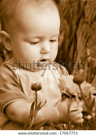 child studies flowerses,small boy,cognition of the world tone sepia child