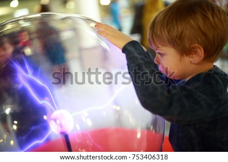 Child studying electrical discharges in a lab