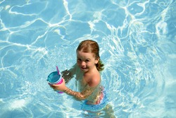 Child swimming in pool. Kids summer vacation. Summertime. Attractions concept Swimmingpool