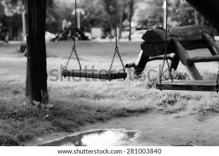 Child swing. Made from wood, hanging on chains. Photographed in a late afternoon, in a park near Palic lake, Serbia.