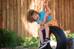 Child swing on backyard. Kid playing oudoor. Happy cute little boy swinging and having fun healthy summer vacation activity
