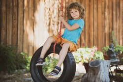 Child swing on backyard. Kid playing oudoor. Happy cute little boy swinging and having fun healthy summer vacation activity.