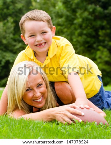 stock-photo-child-tackling-mom-while-playing-football-together-outdoors-147378524.jpg
