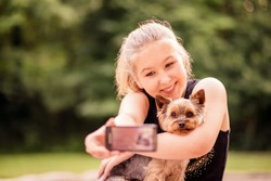 Child taking photo of herself and her dog - outdoor in nature