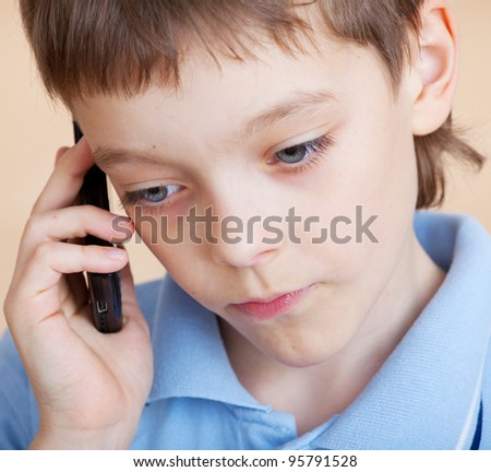 Child, talking on the phone. Sad boy talking on mobile phone