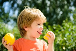 Child taste sour lemon. Eats the lemon boy, expression by the acid. Beautiful little kid boy with citrus on nature green background. Happiness emotions. Citrus fruit for health