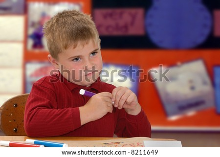 Child thinking about what to color with markers