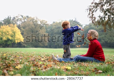 child throwing autumn leafs - stock photo