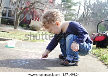 Child, toddler boy drawing with chalk on a sidewalk