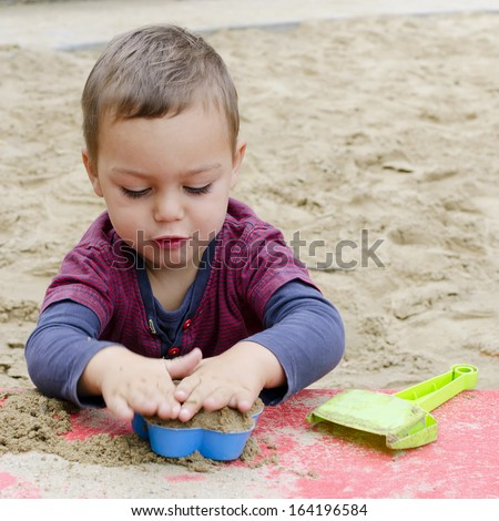Child toddler, boy or girl, playing in sandpit with plastic toys.