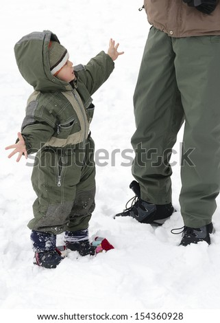 Child toddler in winter snow showing his cold hands to a father or parent.
