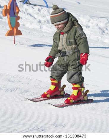 Child toddler learning to ski in winter skiing resort.