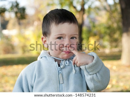 Child toddler picking up his nose.