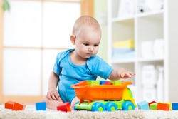 child toddler playing wooden toys at home or kindergarten