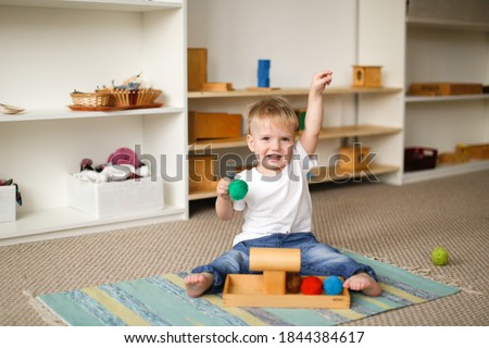child toddler plays with balls and cylinders, developing sensory activities in montessori and earlier development of children, independence of babies ストックフォト ©
