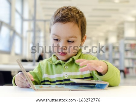 Child toddler reading children picture book on low table in public library.