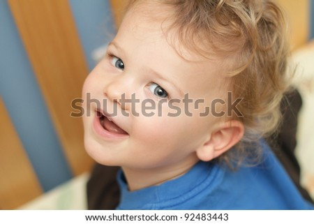 Child, toddler, sitting in a crib or bed - stock photo