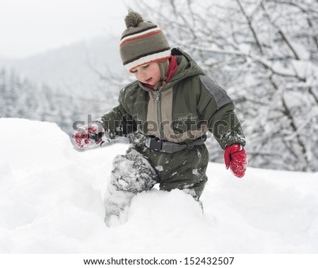Child toddler standing and walking through a deep fresh snow in winter.