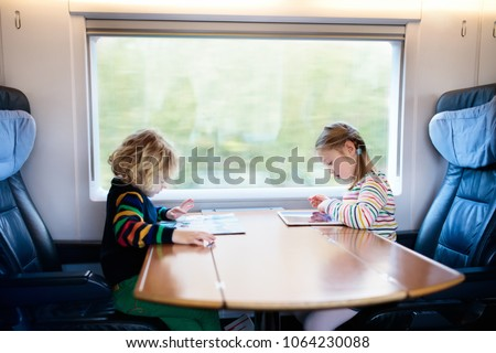Child traveling by train. Little kid in a high speed express train on family vacation in Europe. Travel by railway. Children in railroad car. Kids in rail way wagon. Entertainment for young passenger.