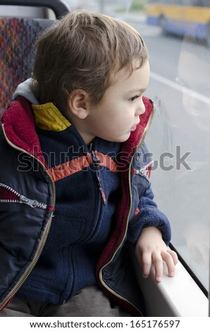 Child traveling on a public city bus looking from the window.