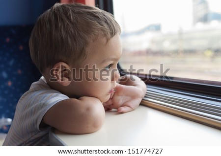 Child traveling on train looking through the window.