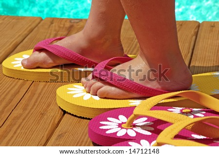 Child trying on flipflops on deck next to pool