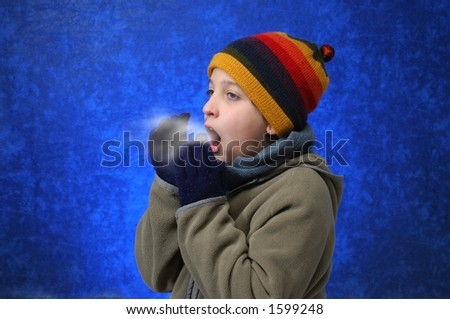Child trying to warm his hands with his breath in winter outfit. - stock photo