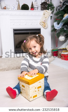 Child under the Christmas tree near the fireplace opens gift. Little girl with open box with a gift near the Christmas tree