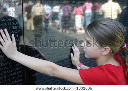 Criança que vê a parede do memorial de Vietnam