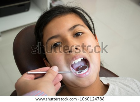 Child visits the dentist, sitting in his chair and opened her mouth.