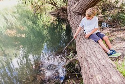 Child waits patiently for a fish to bite from his hook while fishing in a river.