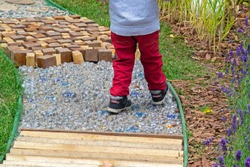 Child walking along garden path made as massage road for feet (different waste: wooden sticks, cubes, plastic bottles, small stones, round cuts of trees). Folk medicine, acupuncture. Selective focus