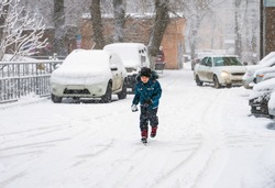 child walking in snow fall next to parked cars
