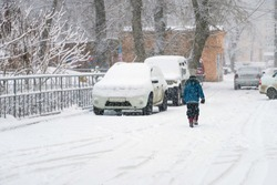 child walking in the snow next to parked cars. Back view