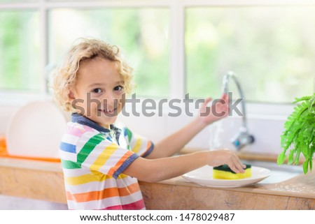 Child washing dishes. Home chores. Kid in white kitchen cleaning plates after lunch at window. #1478029487