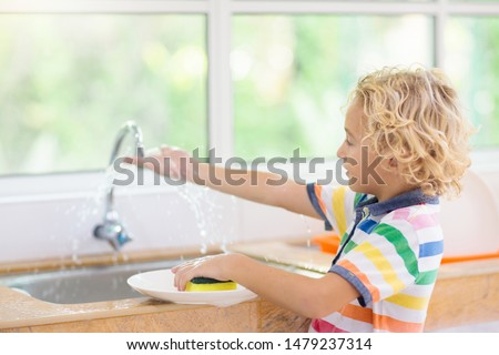 Child washing dishes. Home chores. Kid in white kitchen cleaning plates after lunch at window. #1479237314