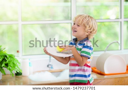 Child washing dishes. Home chores. Kid in white kitchen cleaning plates after lunch at window. #1479237701
