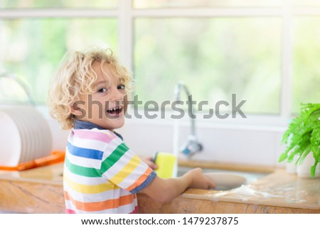 Child washing dishes. Home chores. Kid in white kitchen cleaning plates after lunch at window. #1479237875