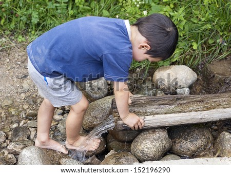 Child washing his feet at nature water stream.
